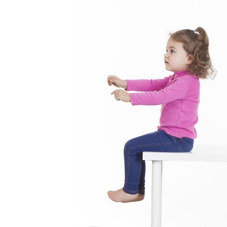 kinderen: Zijaanzicht van meisje zittend op een stoel tegen een witte achtergrond. Geïsoleerde, studio-opname