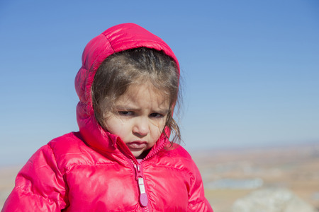 whining: Portrait of cute little girl sadly looking at camera. Blue sky on background. Bokeh.
