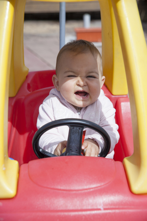 squint: Close-up of funny little girl driving toy car with squint eyes and open mouth