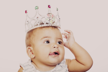 Close-up of little girl wearing fancy crown and showing tongue. Studio shot