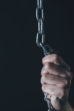 captivated: Mans hand holding silver chain against of black background.