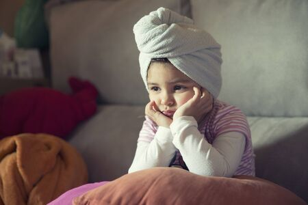 lean on hands: Close-up of little upset girl leaning her head on hands while looking away Stock Photo