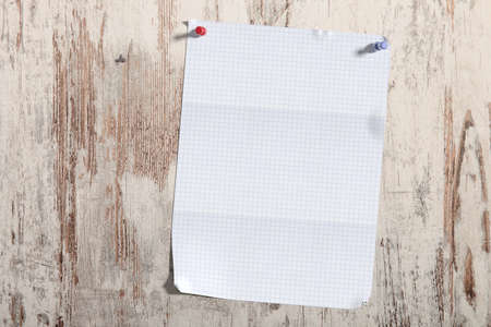 pinned: 3d rendering of a sheet of checked paper pinned on vertical wooden planks.