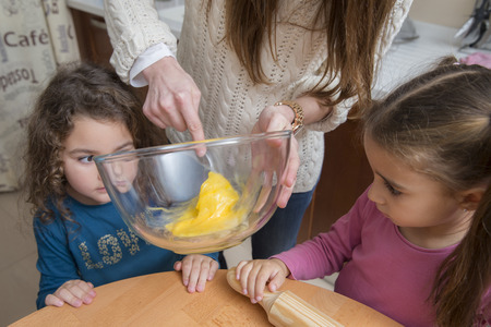 ni�os ayudando: Madre que ayuda a los ni�os para mezclar la yema en un recipiente de vidrio