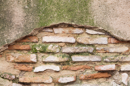 worn structure: Close-up of worn out wall made of bricks and stone covered with moss