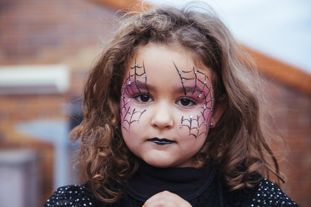 Little girl with spider web painted on face looking at camera. Halloween
