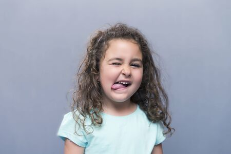 squinting: Portrait of cute curly-haired girl showing tongue and squinting eyes.Isolated
