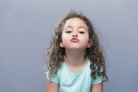 air kiss: Portrait of little girl with curly hair making air kiss to camera.Studio shot Stock Photo