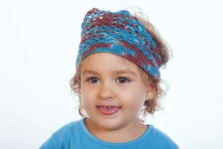 sacar la lengua: Retrato de niña adorable con diadema de sacar la lengua contra el fondo blanco