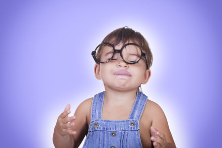 imagines: Studio portrait of cute kid in glasses imagines some yummy food with eyes closed licking lips.Isolate.Blue background.
