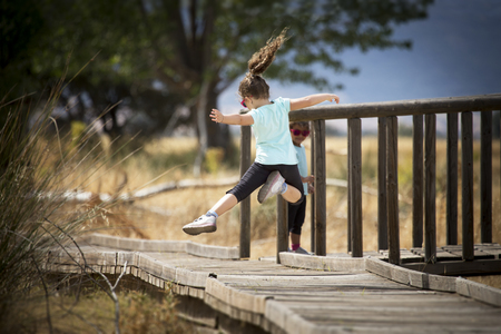 Back view of little girl with tail jumping in mid-air above wooden sidewalk with arms widened. her sister standing on wooden bridge in background.