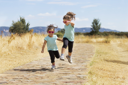 similar: Portrait of little girls in similar wear jumping holding hand in hand along stone path in park in sunlight.