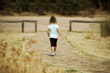 empedrado: Vista posterior de la chica solitaria irreconocible que se va en la tierra de piedra en el campo Foto de archivo