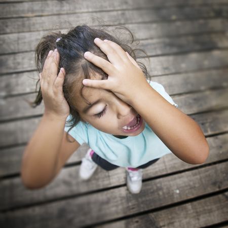 shouting girl: Shouting girl with eyes closed holding her head. Stock Photo