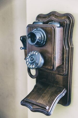 Vintage wooden phone hanging on a wall. Vertical indoors shot Stock Photo