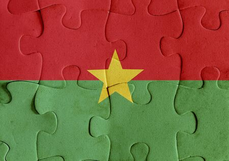 Illustration of a flag of Burkina Faso over some puzzle pieces. Its a JPG image. Stock Photo