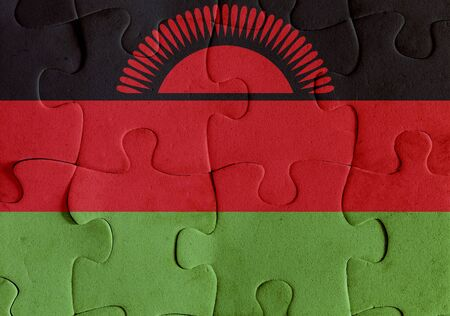 Illustration of a flag of Malawi over some puzzle pieces. Its a JPG image.