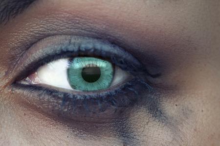 sobbing: Horizontal close-up shot of the a green eye of a sad woman with bleeding makeup.
