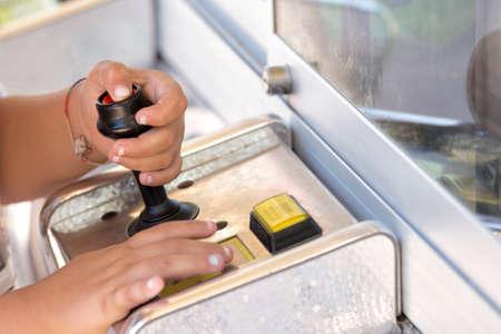 A kid pressing button on joystick. Horizontal outdoors shot
