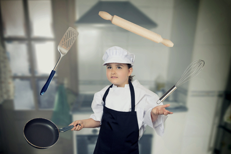 Six years cook girl juggling with some kitchen elements. Stock Photo