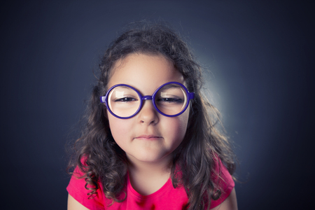 Caricature of six years girl with glasses and a myopic problem. Studio shot. Black background Stock Photo