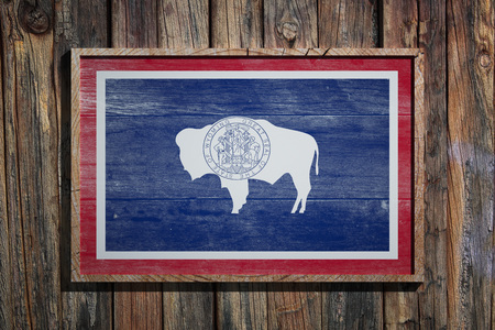 3d rendering of a Wyoming State USA flag on a wooden frame and a wood wall  Stock Photo