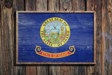 3d rendering of a Idaho State USA flag on a wooden frame and a wood wall  Stock Photo