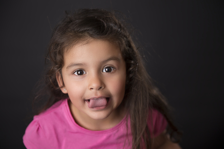 Cute baby girl showing tongue at camera against of black background.
