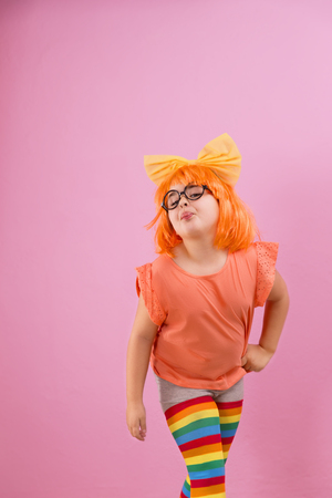 Beautiful seven years girl with an orange wig sticking out her tongue on a pink background