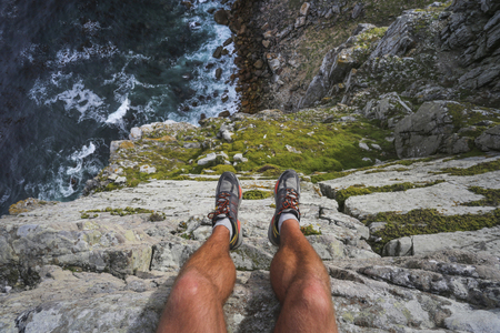 Hiker's legs hanging over the edge of a cliff with the blue ocean far beneath.