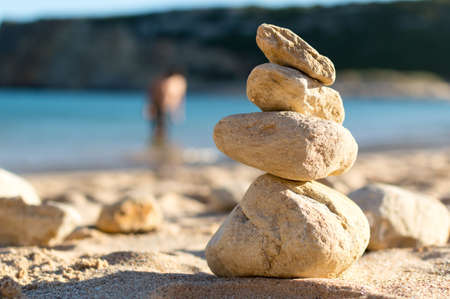 bather: Stone on top of another, also called apacheta that comes from Quechuam and Aymara, was put as an offering to the gods. It has become a fashion when tourists go to the beach and take the typical photo.