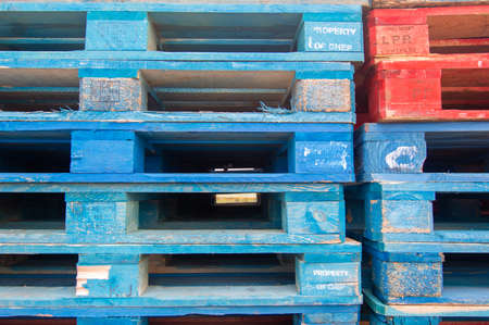 Colorful wooden pallets stacked on top of each other in a factory for stacking fruit boxes.