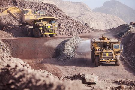 Loading of copper ore on very big dump-body truck and watering road tanker Foto de archivo