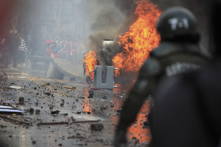 demonstration: Car overturned and burnedStreet damage caused during a student strike in Santiagos Downtown, Chile.