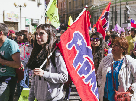 Valparaiso, Chile - August 21, 2016: A young woman carries a FPMR flag, Frente Patriotico Manuel Rodriguez (Manuel Rodriguez Patriotic Front) during a march against pension system. Chileans marched through Valparaisos streets, demanding an end to the p