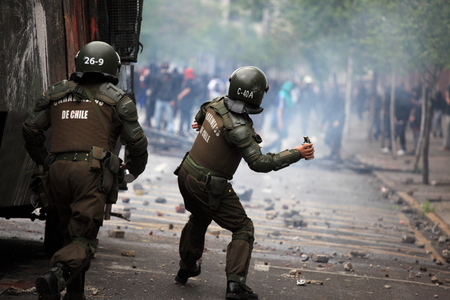 Santiago, Chile - October 06, 2011: Riot police launching tear gas at protesters during a student strike in Santiagos Downtown, Chile. Protesters demand the government to improve education quality.