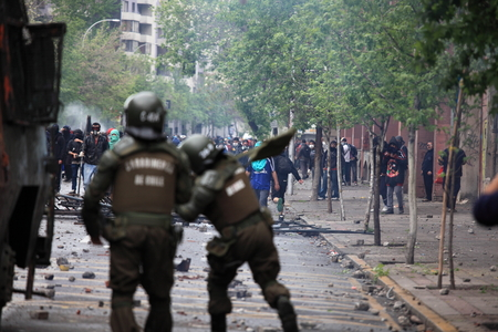 granade: Santiago, Chile - October 06, 2011: Riot police launching tear gas at protesters during a student strike in Santiagos Downtown, Chile. Protesters demand the government to improve education quality.