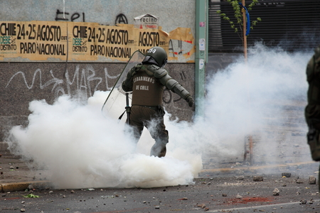 granade: Santiago, Chile - October 06, 2011: Riot police kicks a tear gas canister that was launched during a student strike in Santiagos Downtown, Chile. Protesters demand the government to improve education quality.
