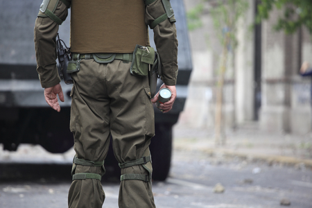 Riot police tear gas bomb in With His hands.Santiago, Chile.