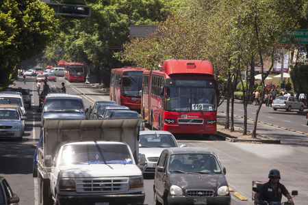 Mexico City, Mexico- May 30, 2012: View of a row of Line 1 Metrobuses heading to Caminero at a the Insurgentes Avenue. Insurgentes is considered the longest avenue in the world. Редакционное