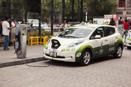 Mexico City, Mexico - June 7, 2012: A Nissan electric car used as a taxi is being charged at the charging station behind the capitals towering cathedral, as part of an agreement between the auto maker and the local government to promote the use of enviro Редакционное