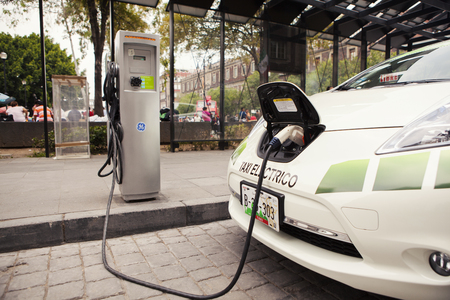 Mexico City, Mexico - June 7, 2012: A Nissan electric car used as a taxi is being charged at the charging station behind the capitals towering cathedral, as part of an agreement between the auto maker and the local government to promote the use of enviro Sajtókép