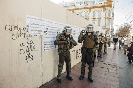 Valparaiso, Chile - June 01, 2017: Chilean riot police shoot Protestants during a march on the streets of Valparaiso, following President Michelle Bachelets annual state-of-the-union speech to Congress.