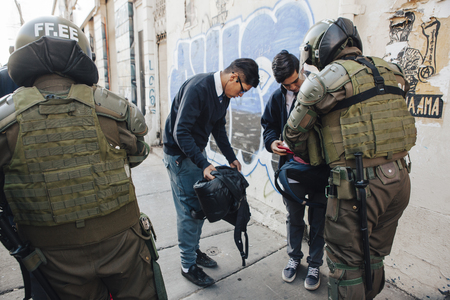 Valparaiso, Chile - June 01, 2017: Riot Police check backpacks during a march in Valparaiso, following President Michelle Bachelets annual state-of-the-union speech to Congress. Редакционное