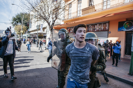 protester: Valparaiso, Chile - June 01, 2017: Protester arrested by the Chilean riot police during a protest in the center of Valparaiso, following President Michelle Bachelets annual state-of-the-union speech to Congress.