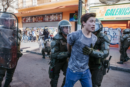 Valparaiso, Chile - June 01, 2017: Protester arrested by the Chilean riot police during a protest in the center of Valparaiso, following President Michelle Bachelets annual state-of-the-union speech to Congress. Фото со стока - 80139700