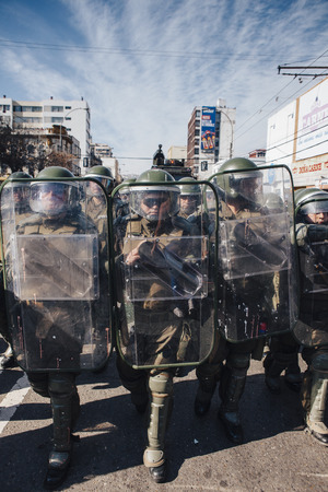 Valparaiso, Chile - June 01, 2017: Chilean riot police repress Protestants during a march on the streets of Valparaiso, following President Michelle Bachelet's annual state-of-the-union speech to Congress. Фото со стока - 80139758