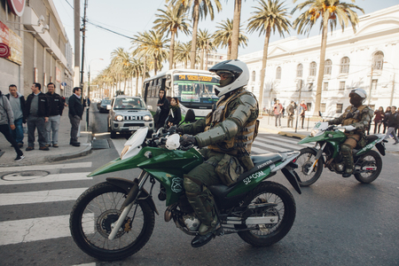 Valparaiso, Chile - June 01, 2017: Police on motorcycle repressing protesters during a protest in Valparaiso Редакционное