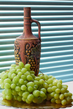 Jug of wine and grapes