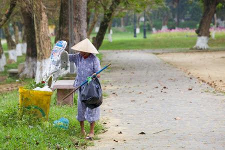 recolector de basura: Hue, Vietnam - 07 de marzo: La mujer mayor recoge cosas de la basura en el parque público el 7 de marzo de 2014 en Hue, Vietnam.